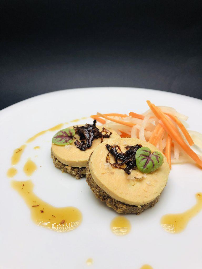 2. Пастет от патешки дроб сервиран върху ръжен хляб с квас, пияни сини сливи, и гарнитура от морков и земна ябълка.