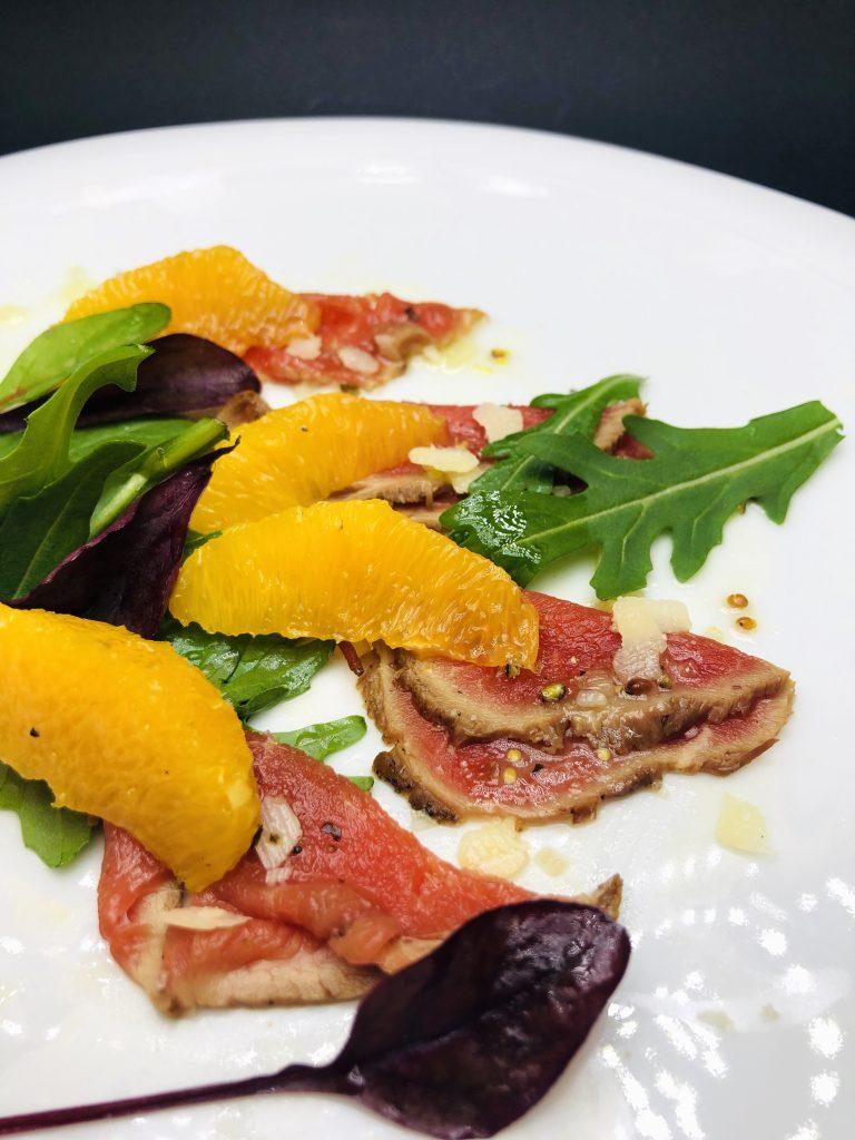 3. Карпачо от телешко бон филе Ангъс, с розов пипер, пармезан и сол Малдон, гарнирано с белени портокали и бейби салатки.