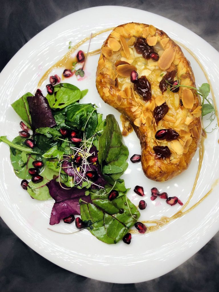 4. Печена круша в бутер тесто, пълна със сирене Горгонзола, филирани бадеми и шипково сладко, в комбинация с бейби салати и нар.
