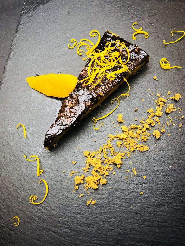 5. Шоколадово-портокалов веган чийзкейк, направен със сирене от кашу и основа от фурми, чия, ядки и кокос