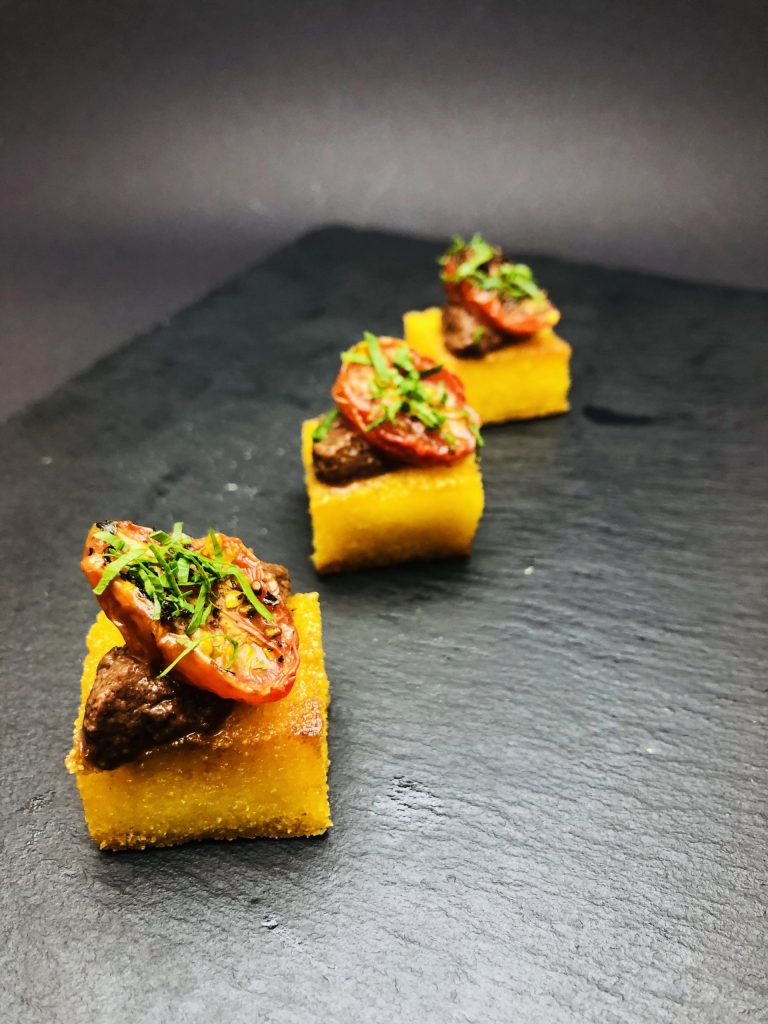 1. Crispy polenta base with olive tapenade from three types of olives and lightly baked cherry tomatoes.