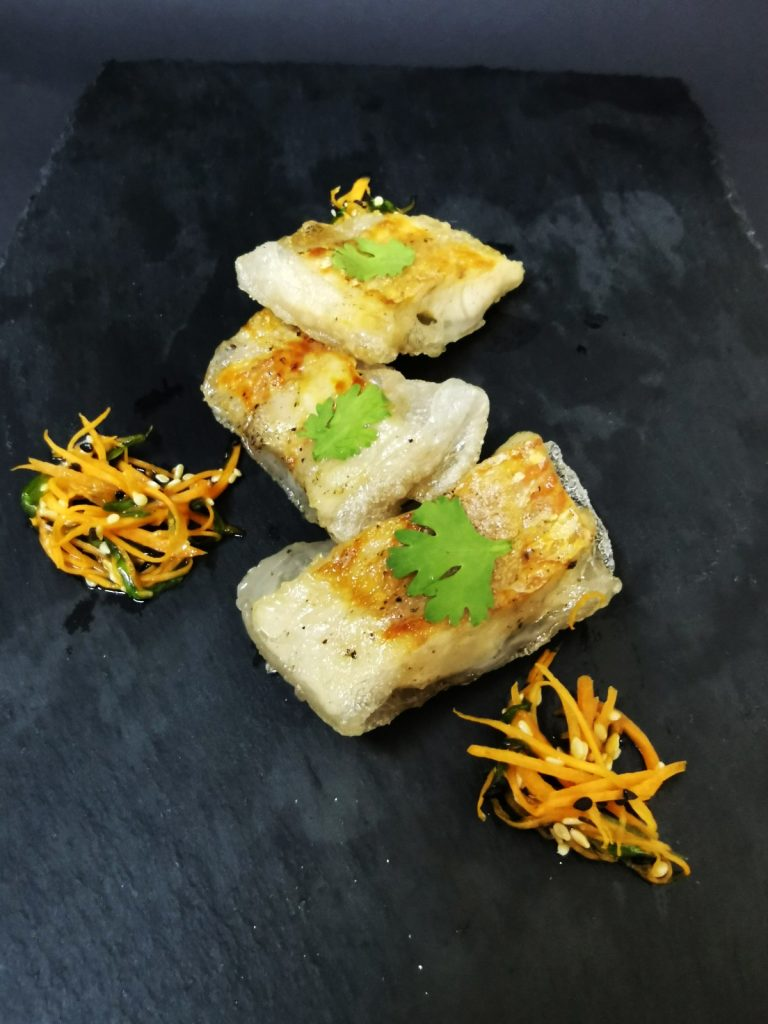 1. Cod fish with 5 spices in rice pastry, garnished with Asian salad with carrots, green onions and sesame.